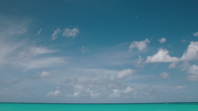 WS of plane in distant sky and Maho Beach / St. Maarten