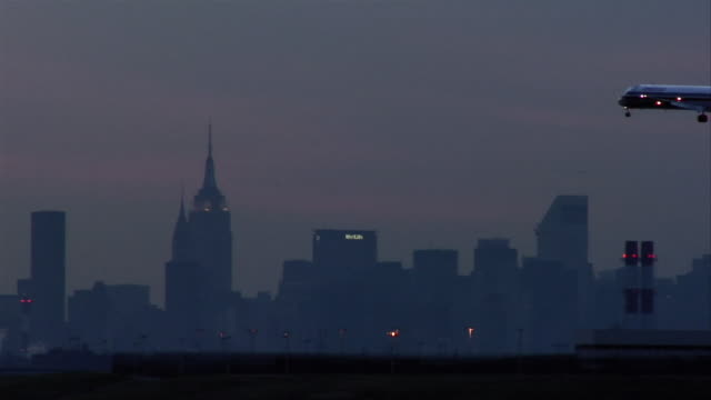 WS plane landing at LaGuardia airport at dusk with Manhattan skyline in background/ New York City