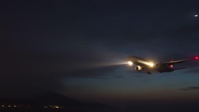 plane landing at night in phuket international airport,phuket,thailand. - autoscheinwerfer stock-videos und b-roll-filmmaterial