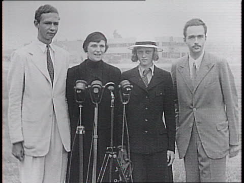 Plane lands at La Guardia Field / former Empress Zita of Austria walks past camera smiling with sons Archduke Felix and Archduke Otto and her...