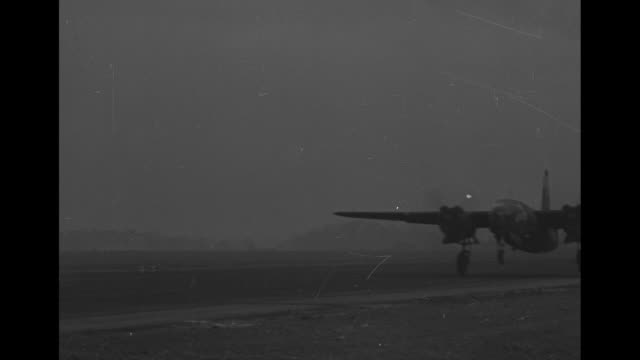plane lands, ground flare sparks at side of runway / smoke rises from field at dusk / group of airmen stand together near bunker and truck, one man... - world war ii video stock e b–roll