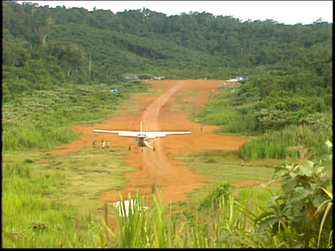 A plane lands on a jungle runway servicing a gold mine in the Amazon