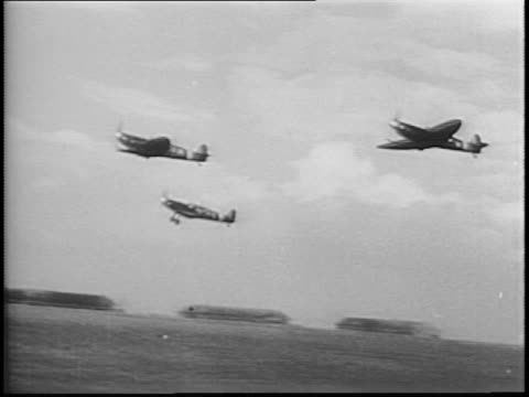 plane propeller spins and pilot gives thumbs up / three planes taking off / soldier stencils poland symbol on side of plane / mustang planes take off... - アロマンシェス点の映像素材/bロール