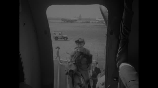 plane taking off from idlewild airport in ny city / inside plane model walks down aisle towards camera and displays suit she is wearing / plane on... - galeere stock-videos und b-roll-filmmaterial