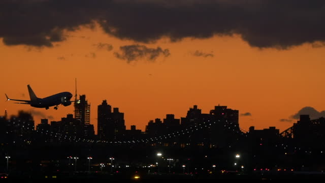 plane taking off in new york city at twilight - commercial aircraft stock videos & royalty-free footage