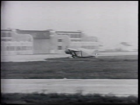 plane taxiing on grass, across strip, too fast for turn, hitting something, wings collapsing, catching fire, burning w/ building sign 'erickson... - 航空事故点の映像素材/bロール