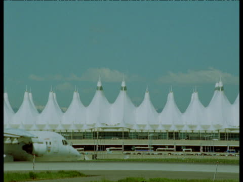 stockvideo's en b-roll-footage met plane taxis in front of terminal building, denver airport - dia