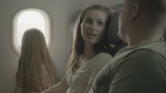 plane travel. family holiday. parents are chatting in their seats, while their excited little girl is looking out of the window. mother turns to look... - chroma key stock videos & royalty-free footage