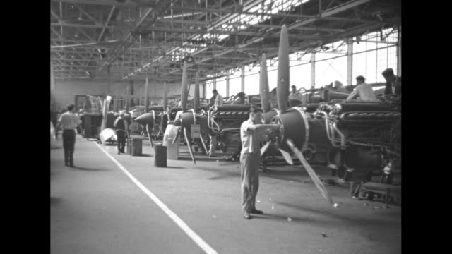 Plane wheel moving down from fuselage worker watching mechanism / plant section with plane tails lined up and workers / motors with propellers lined...