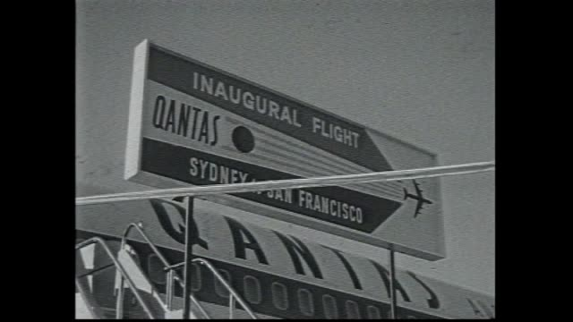 QANTAS plane with Australian flag on cockpit / sign QANTAS Inaugural Flight Sydney to San Francisco / flight crew and hostess stand lined up on...