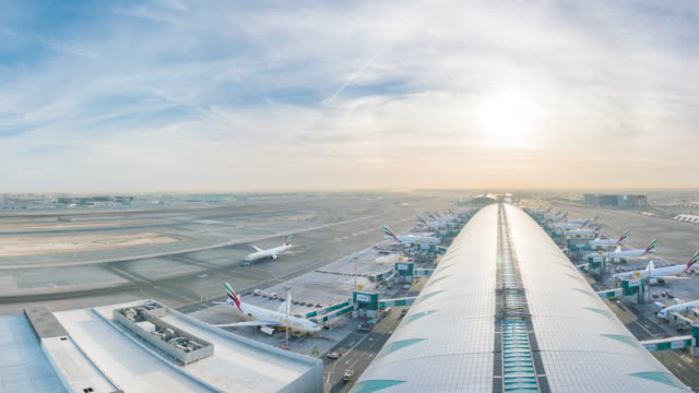 stockvideo's en b-roll-footage met planes arriving at gate daytime, dubai airport, dubai - blijf staan