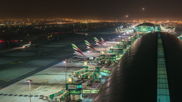 planes arriving at gate night, dubai airport, dubai - flughafen stock-videos und b-roll-filmmaterial