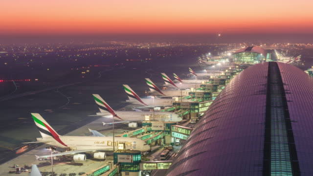 planes arriving at gate sunrise, dubai airport, dubai - vereinigte arabische emirate stock-videos und b-roll-filmmaterial