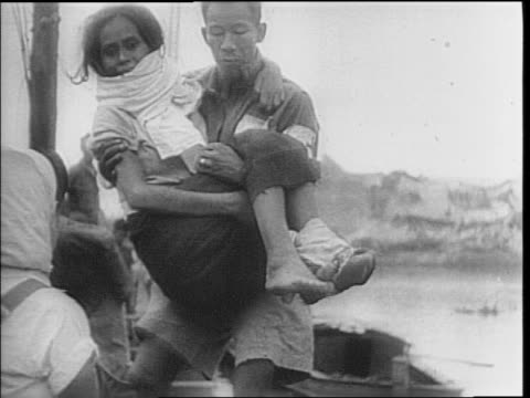planes fly in sky over barrel of smoking gun / filipino civilians cross bridges many wounded or carrying children / soldiers care for a sick boy /... - {{relatedsearchurl(carousel.phrase)}}点の映像素材/bロール