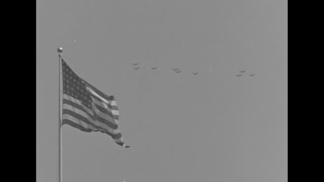 Planes flying in formation American flag flying on ground at US Military Academy / planes flying pan to include flag in fg / WS marching cadets on...