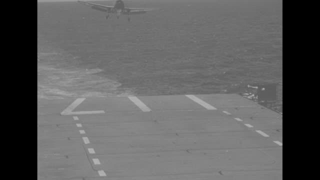 vídeos de stock, filmes e b-roll de vs planes landing on deck of carrier uss saidor / landing signal officer waving off plane plane flies low past him / view from side of deck of plane... - oceano pacífico do sul