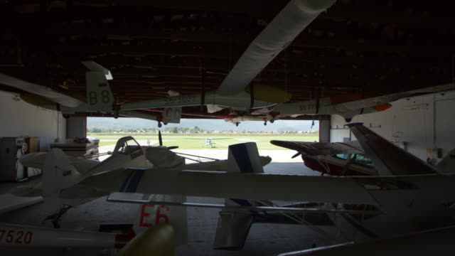 cs planes parked in the hangar and two men opening the hangar door - private airplane stock videos & royalty-free footage