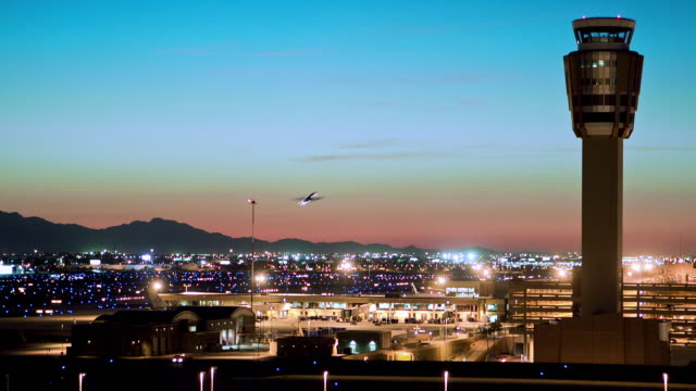 WS T/L Planes taking off from Phoenix Airport against silhouette of Arizona mountains with control tower / Phoenik, Arizona, USA