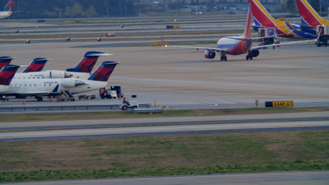 planes taxiing at the atlanta international airport terminal at night - southwest usa stock-videos und b-roll-filmmaterial