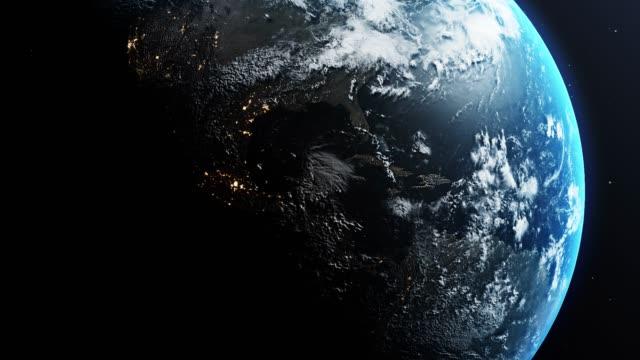 vídeos de stock, filmes e b-roll de planeta terra está girando no espaço exterior contra fundo negro com estrelas - espaço para texto