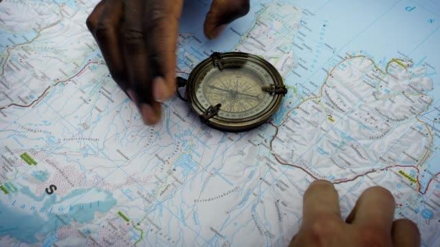 reiseplanung mit karte und kompass - kompass stock-videos und b-roll-filmmaterial