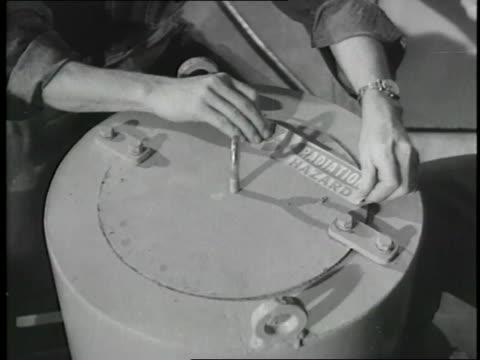 a plant worker places a radiation hazard label on a container at the first civilian atomic power plant - kernenergie stock-videos und b-roll-filmmaterial