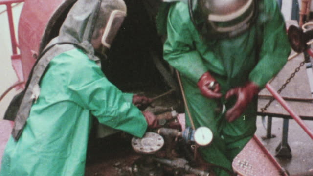 1978 zi plant workers in hazardous material suits unloading molten phenol / united kingdom - 1978 stock-videos und b-roll-filmmaterial