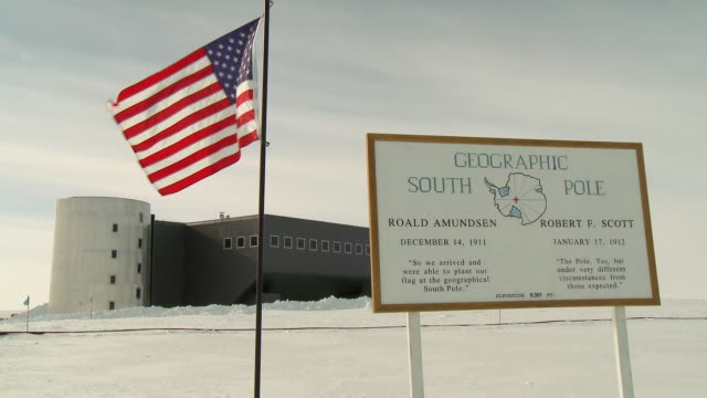 ms of plaque at geographic south pole, us flag and scott amundsen station / south pole, antarctica - south pole stock videos & royalty-free footage