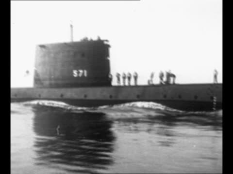 plaque lists details of the uss nautilus / pan nautilus as it moves in water; crew members stand on deck / bow of nautilus moves through ocean as sea... - 船の一部点の映像素材/bロール