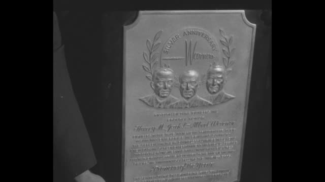 cu plaque with engraved images of three warner brothers / jack harry and albert hold plaque jack cohn to their right - warner bros stock videos & royalty-free footage