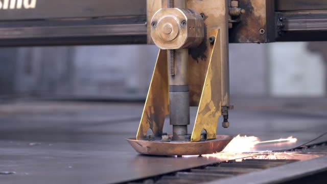 vidéos et rushes de plasma cutting torch head controlled by programmed data moves across sheet metal throwing sparks / redlands, california, usa - tôle