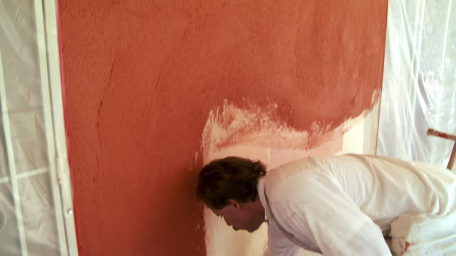 MS Plasterer applying colored plaster on wall / Rancho Mirage, California, USA.