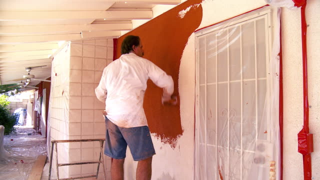 MS ZI Plasterer applying colored plaster on wall / Rancho Mirage, California, USA.