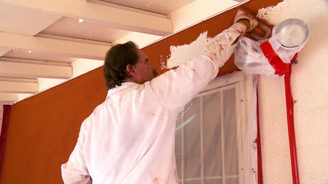 MS PAN Plasterer applying colored plaster on wall / Rancho Mirage, California, USA.