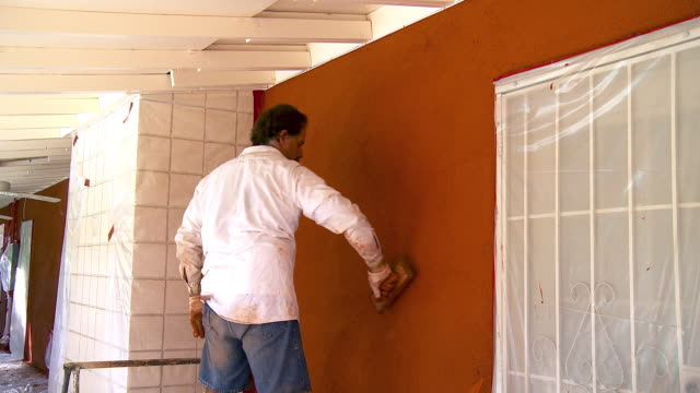 MS Plasterer giving the sandy finishing to plastered wall / Rancho Mirage, California, USA.
