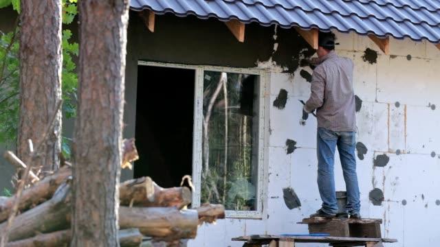 Pleisteren van de buitenste muur.