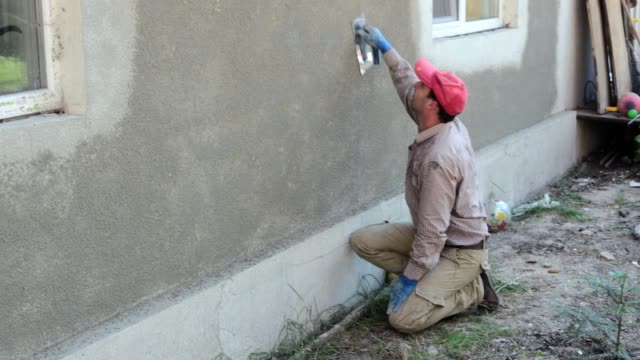 Plastering works. Plasterer smooths irregularities on the wall with the trowel.