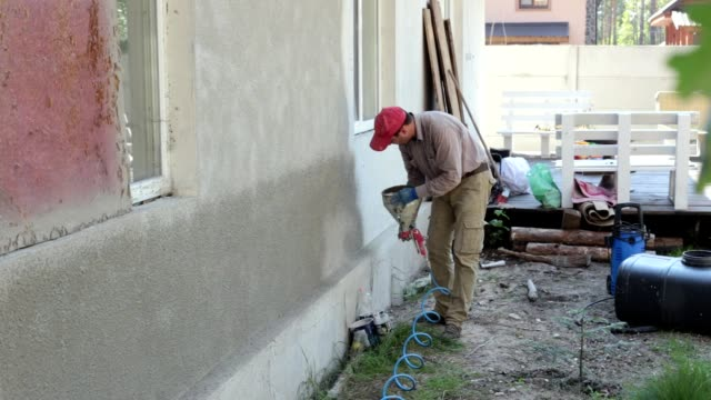 plastering works. the plaster sprays the mortar on the wall. - plaster stock videos and b-roll footage