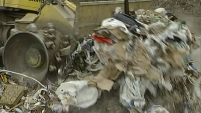 Plastic bag charge introduced in England Taken from T24050721 Piles of rubbish being pushed along by earthmover at landfill site