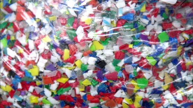 vídeos de stock e filmes b-roll de a plastic bag holds pieces of colorful plastic. - reciclagem