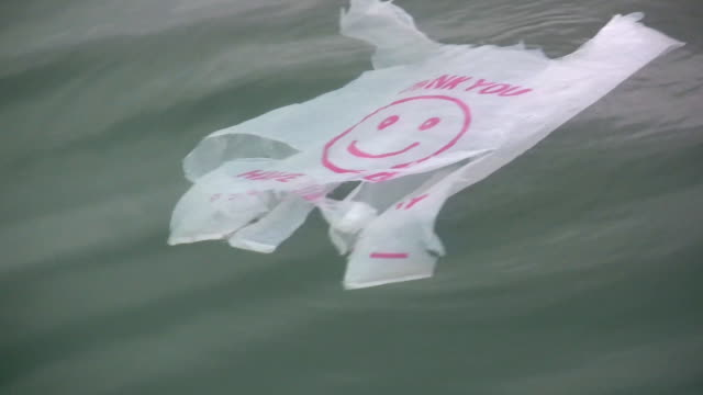 vídeos y material grabado en eventos de stock de cu plastic bag with smiley face on it floating in water / san pedro, california, usa - bolsa de plástico