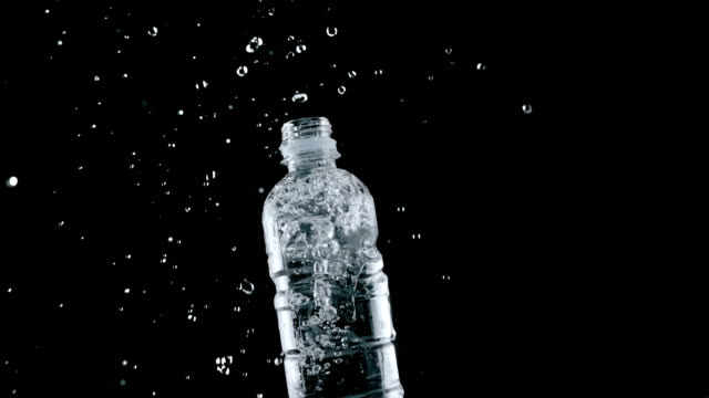 slo mo ld plastic bottle filled with water falling onto a surface and the water splashes around - splashing stock videos & royalty-free footage
