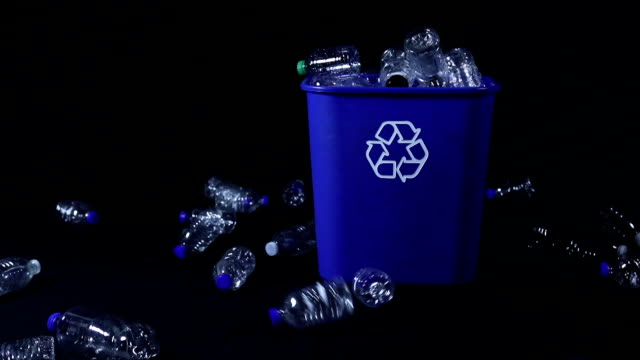 Plastic Bottles Being Tossed At Recycling Bin