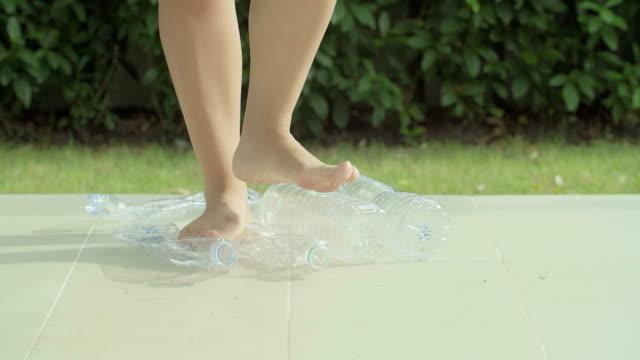 vídeos de stock e filmes b-roll de hd : frascos de plástico reciclagem de um pé colocada. - garrafa