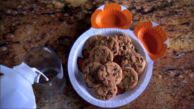 Plastic child's plate in shape of a bear w/ a dozen chocolate chip cookies empty glass on counter top stream of milk pouring into glass from off...