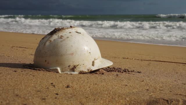 vídeos de stock e filmes b-roll de plastic construction hard hat pollution on a sandy beach - utilização única