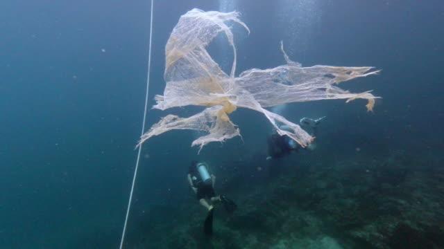 plastic degrading to microplastic near underwater scuba divers - プラスチック汚染点の映像素材/bロール