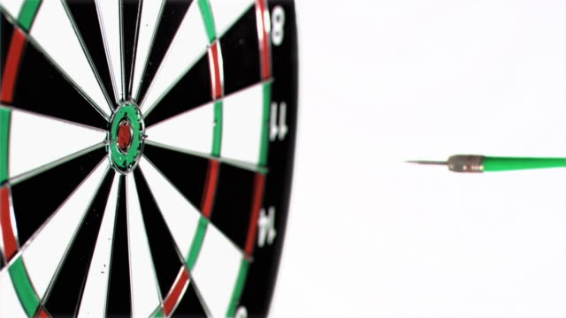 plastic green dart in super slow motion being thrown on a dart board - dart board stock videos & royalty-free footage