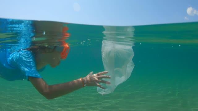plast i havet. barn rengöra havet. miljöfrågor - slit och släng bildbanksvideor och videomaterial från bakom kulisserna