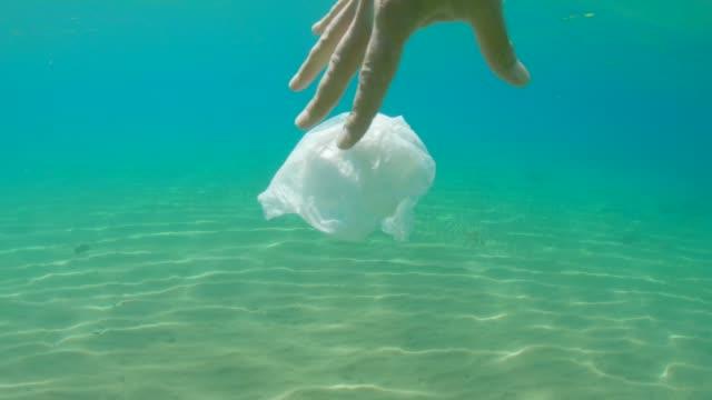 vídeos y material grabado en eventos de stock de plástico en el océano. cuestiones ambientales. limpieza del océano, extracción manual de bolsa de plástico. - flotar sobre agua